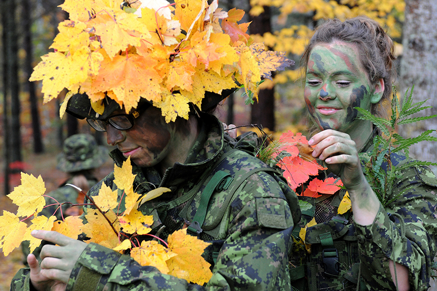 Candidate Heather Kitson (left) of Portage la Prairie, Manitoba, has her foliage adjusted by fellow course member Candidate Mercedes Pinch of Okanagan, British Columbia on October 17, 2013, prior to a stalking exercise at Camp Aldershot in Nova Scotia, in which the candidates have to advance on an observation position from 100 metres away without being detected.