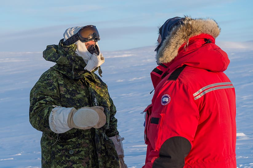 Le major-général Hetherington, commandant du Centre de doctrine et d'instruction de l'Armée canadienne (à gauche), discute avec un membre de l'équipe d'instruction pendant une visite du Centre d'instruction dans l'Arctique à Resolute Bay, (Nunavut), le 24 février 2018. Le Centre est dirigé conjointement par les Forces armées canadiennes et Ressources naturelles Canada. Photo : Caporal-chef Jennifer Kusche, Caméra de combat des Forces canadiennes. ©2018 DND/MDN Canada.
