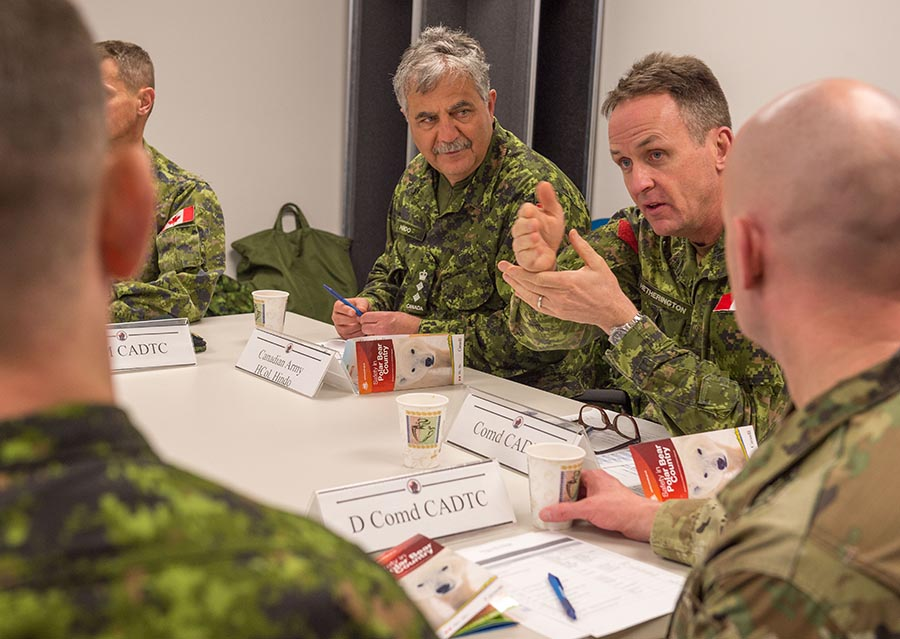 Hononary Colonel of the Canadian Army Paul Hindo (centre) listens as Major General Hetherington, Commander of the Canadian Army Doctrine and Training Centre, (right) makes a point during a visit to the Arctic Training Centre at Resolute Bay, Nunavut on February 24, 2018. Photo: Master Corporal Jennifer Kusche, Canadian Forces Combat Camera. ©2018 DND/MDN Canada.