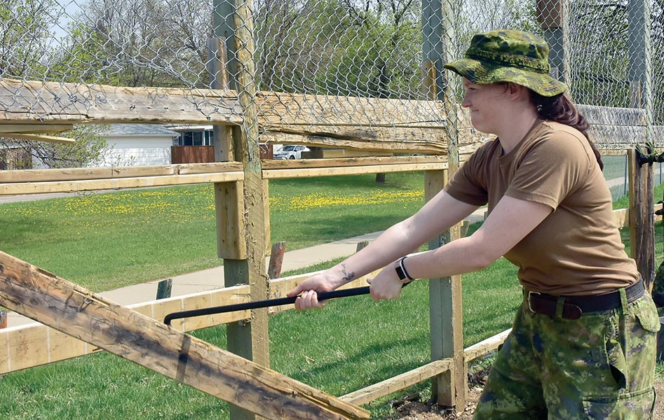A member of Real Property Operations Unit (West) applies her crowbar to a fence demolitio.